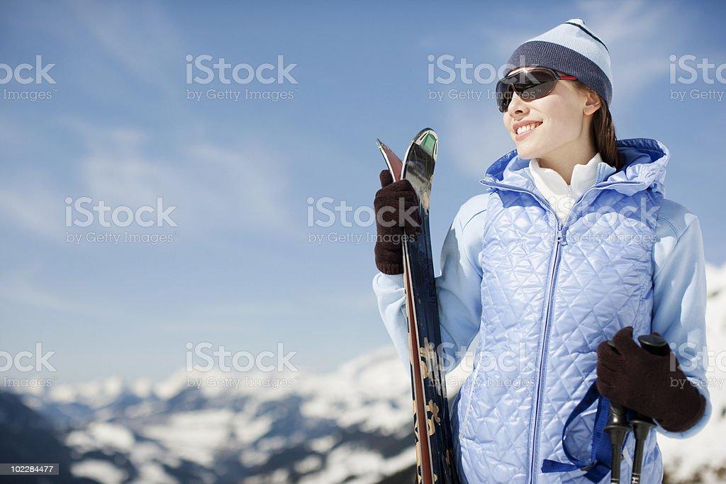 Woman on mountain holding skis royalty-free stock photo