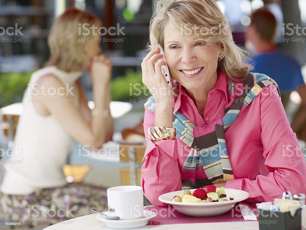 Woman on outdoor patio with her mobile phone and fruit bowl royalty-free stock photo