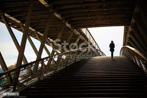 Woman walking on Passerelle Solférino footbridge in Paris, France.