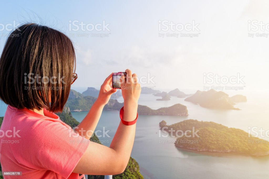 Woman on peak take photos stock photo