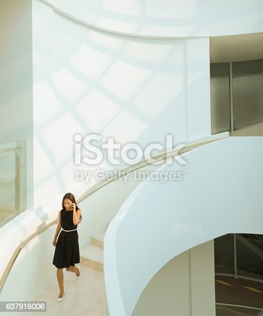Woman on phone descending staircase in modern building
