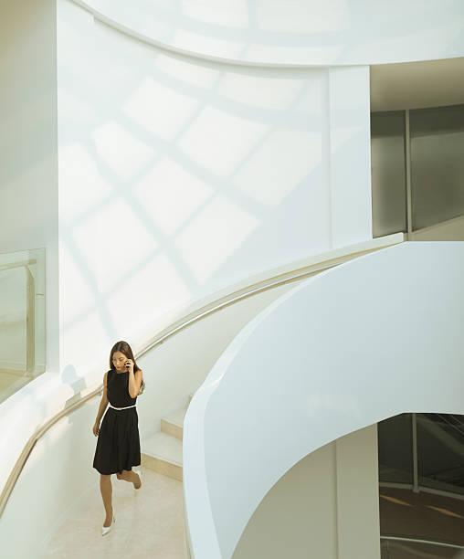 woman on phone descending staircase in modern building - bogen bauen stock-fotos und bilder