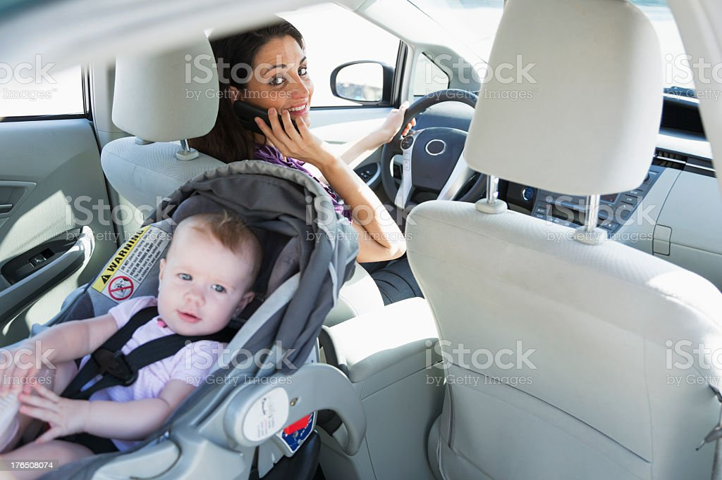 Woman on phone driving with baby stock photo