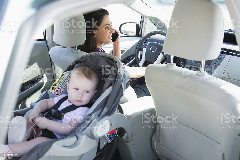 Woman on phone driving with baby royalty-free stock photo
