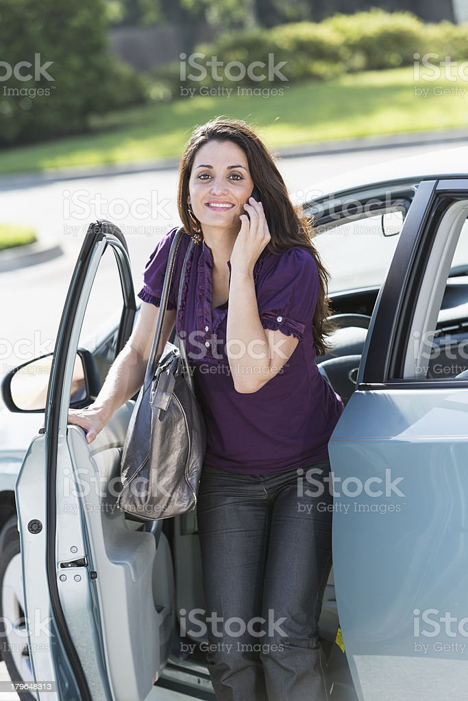 Woman on phone getting out of car royalty-free stock photo