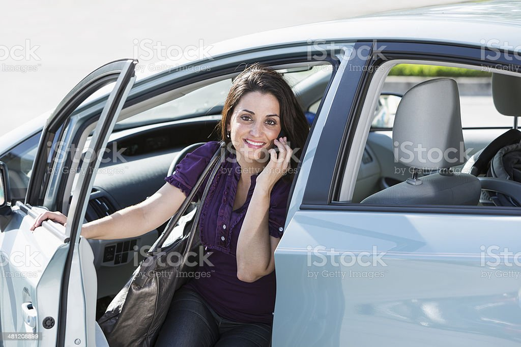 Woman on phone getting out of car stock photo