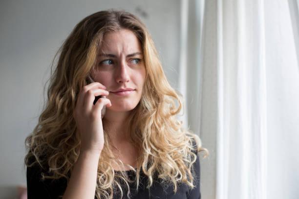 Frau am Telefon im Wohnzimmer – Foto