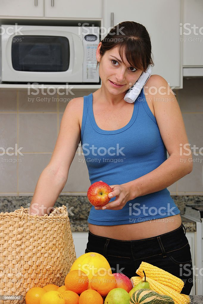 woman on phone unpacking groceries royalty-free stock photo