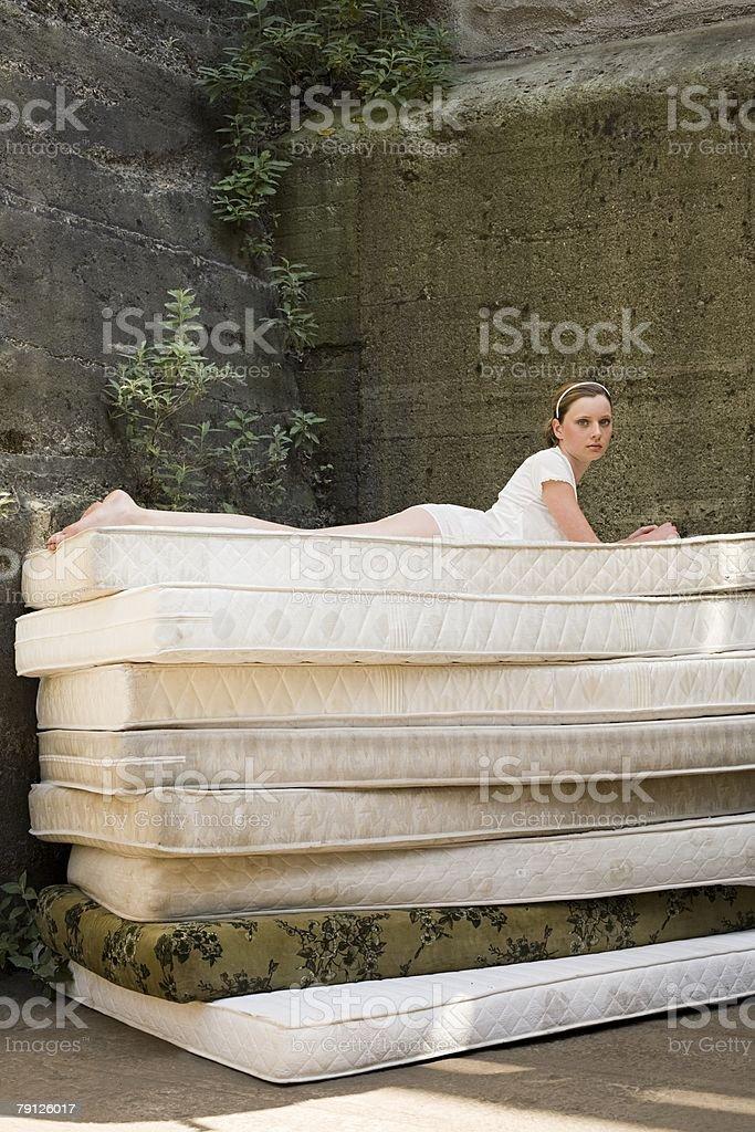 Woman on pile of mattresses 免版稅 stock photo