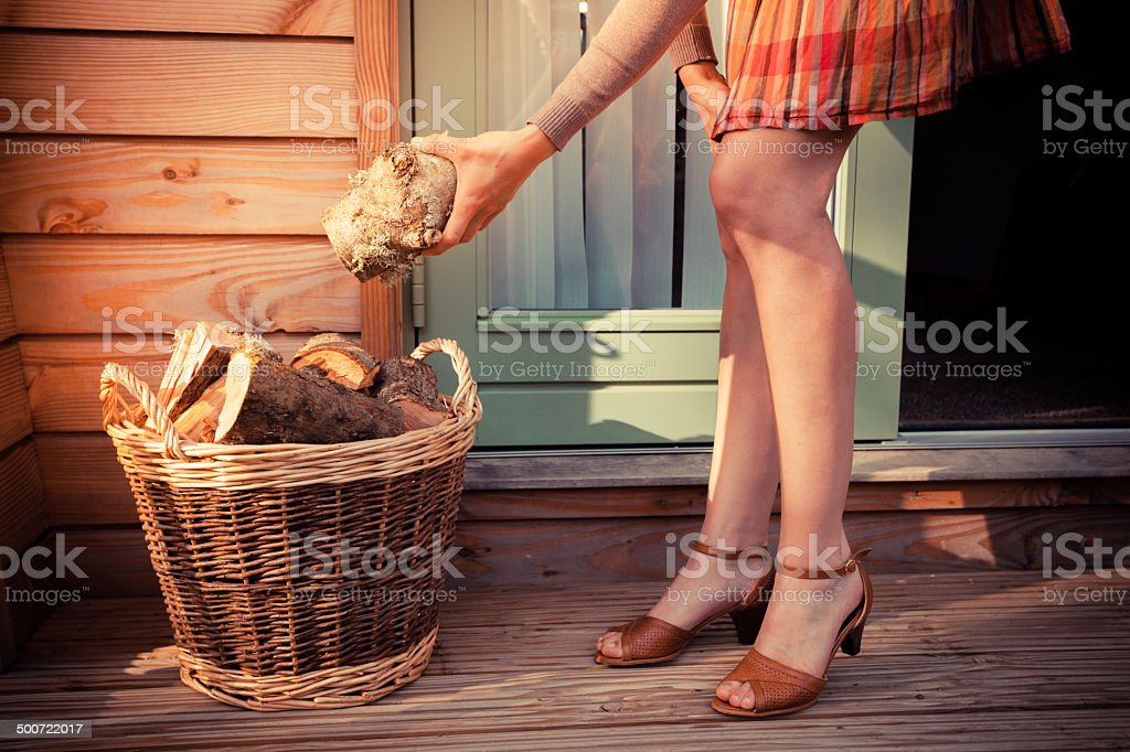 Woman on porch getting logs for firewood royalty-free stock photo