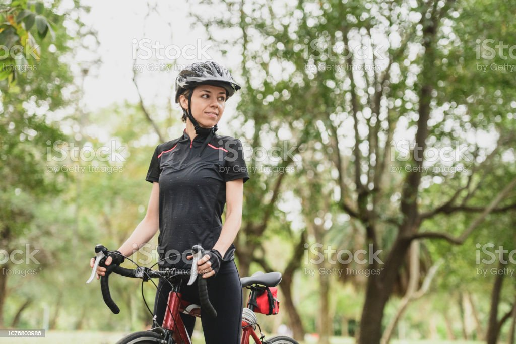 Portrait of woman looking to one side, wearing cycling clothing,...