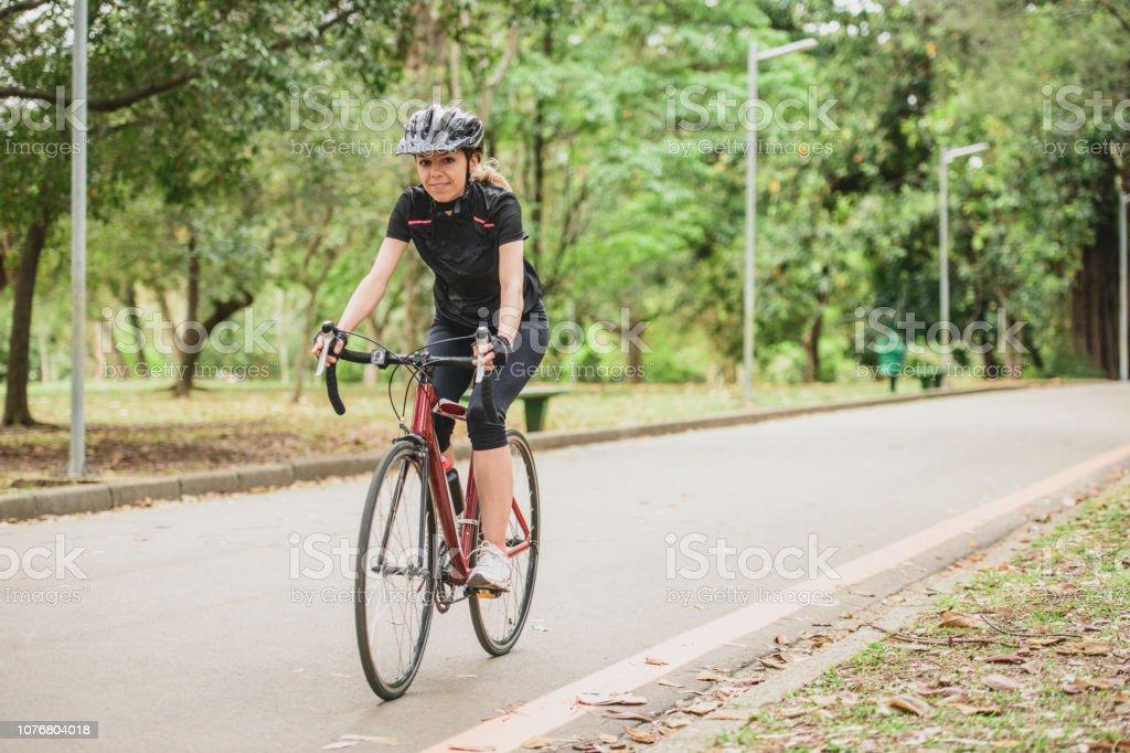 Portrait of woman cycling near woodland, wearing safety helmet,...
