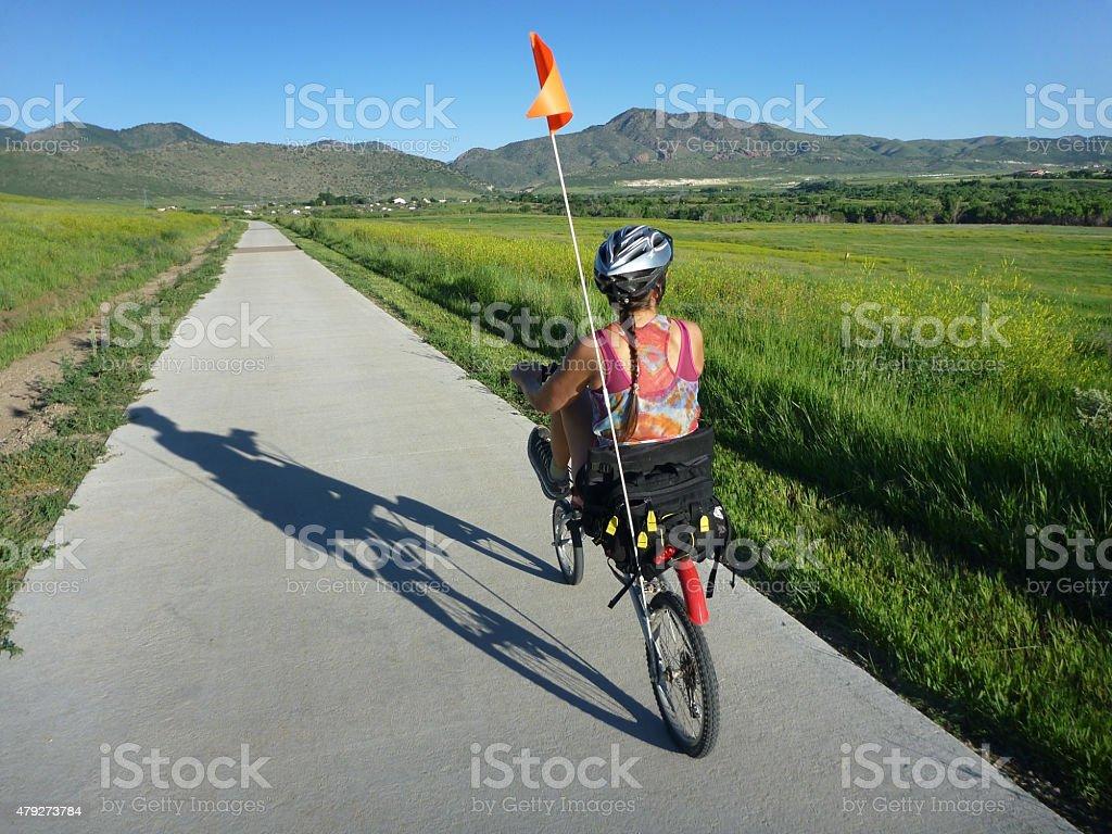 Woman on recumbent bicycle pedals Colorado Bear Creek Lake Park stock photo