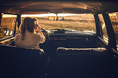 Young woman driving car on beautiful sunny day, getting away from it all alone, rear view, photo is taken in car from 1980 year