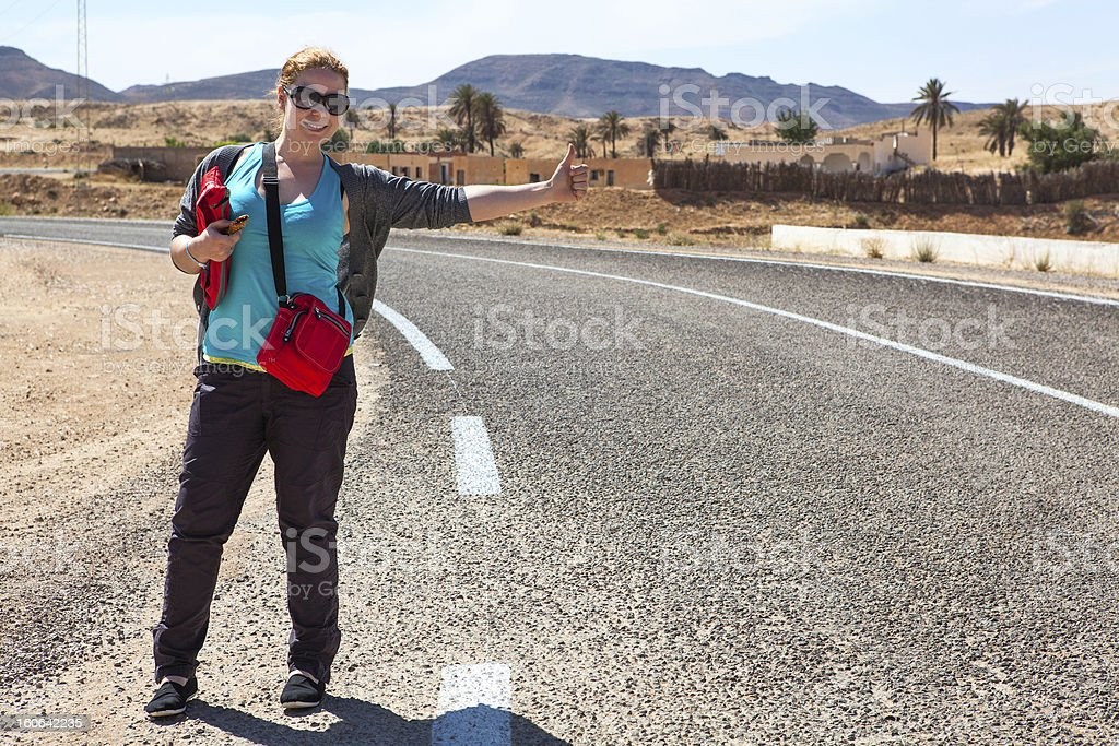 Woman on road with thumb lift up for hitching car royalty-free stock photo
