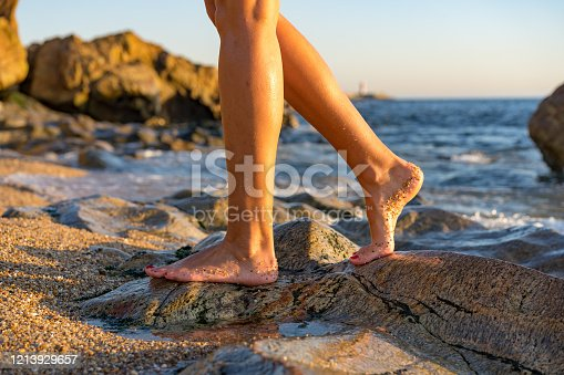 522909925 istock photo Woman on rock at beach dipping toes in water, having fun outdoor lifestyle in Matosinhos, Portugal 1213929657