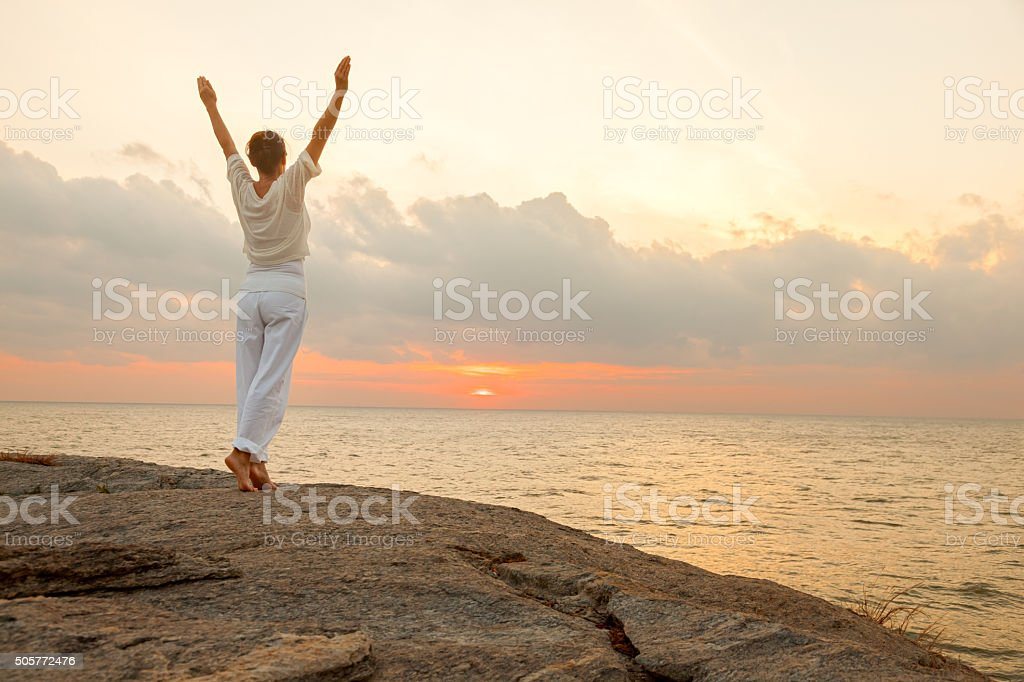 Woman on rock stock photo