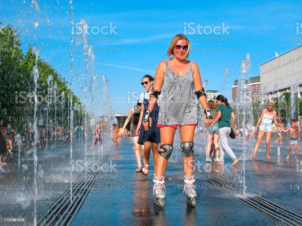 Woman On Roller Skates Smiling Hot Weather Splashing Water