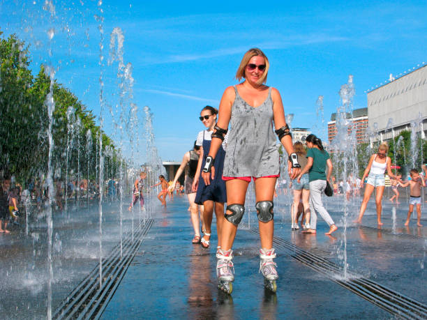 Woman on roller skates, smiling, hot weather, splashing water Moscow, Russia - August 29, 2018: Woman rides on roller skates among  the splashing water of fountain and smiling. She is wearing a T-shirt and shorts, on the knees and elbows sports protection. Summer, hot weather. padding stock pictures, royalty-free photos & images
