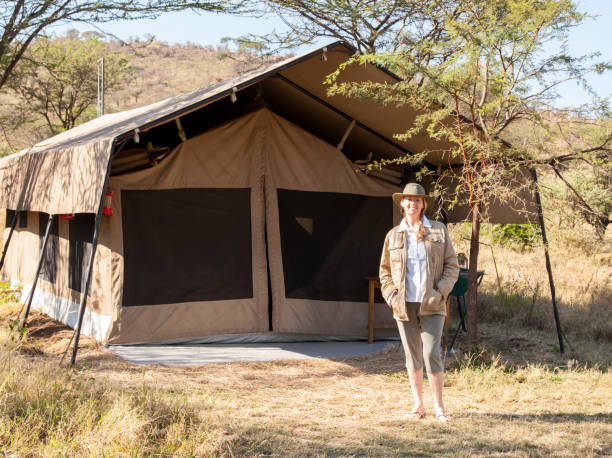 Woman on Safari in Tanzania Stands Outside Her Tent stock photo