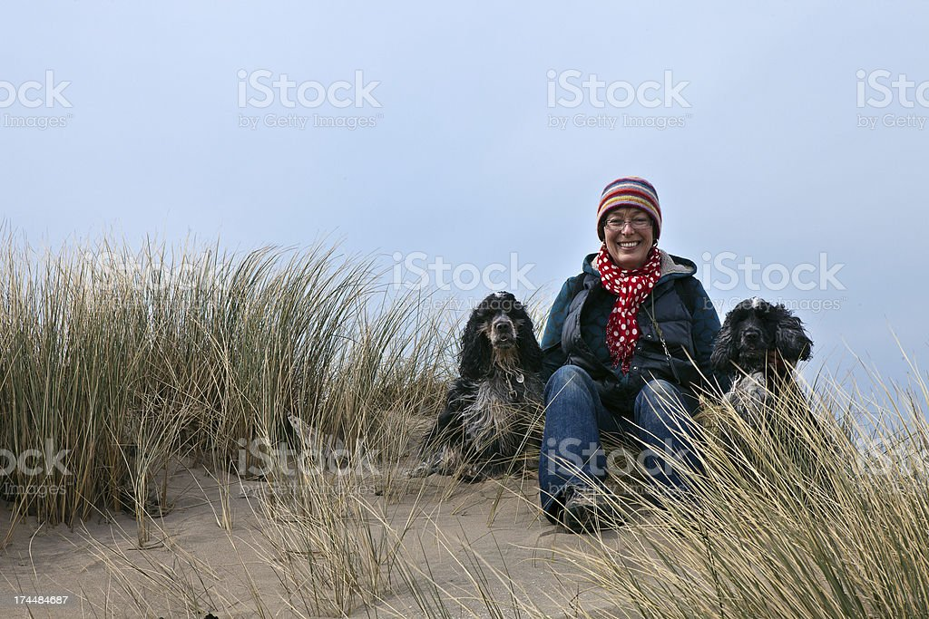 woman on sand dune with two dogs royalty-free stock photo