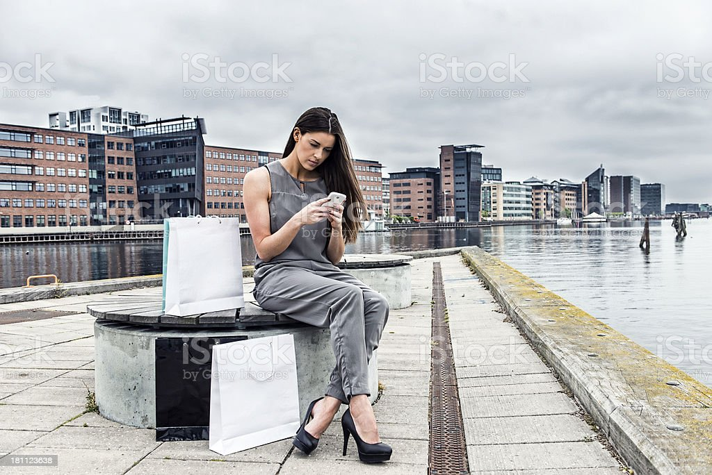 Woman on shopping trip takes a break with smartphone stock photo