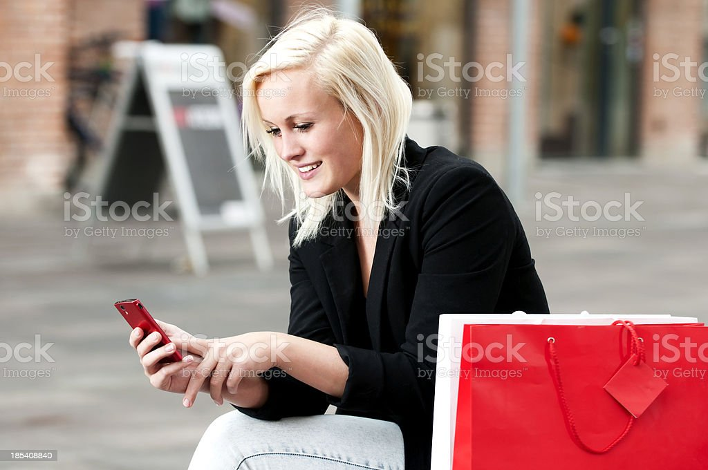 Woman on shopping trip texts on her phone royalty-free stock photo