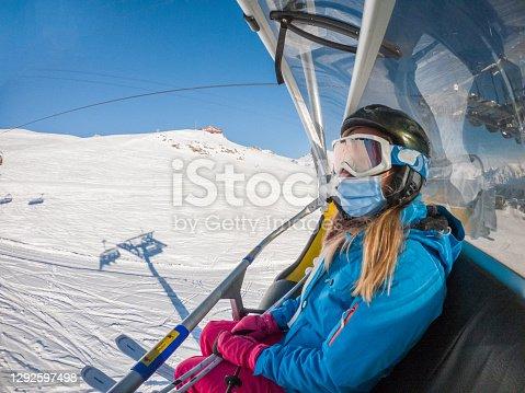 istock Woman on ski lift, Covid-19 1292597498