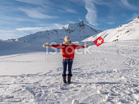 Cheerful young woman on mountain in winter holding Swiss flag in hand, snow winter wonderland