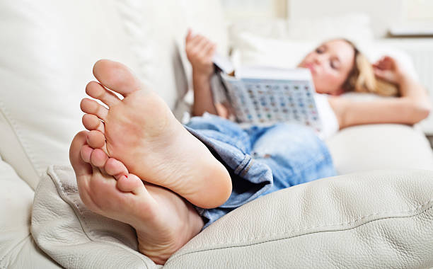 Woman on sofa with book stock photo