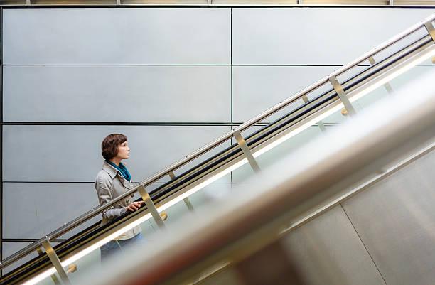 donna alla stazione della metropolitana scale mobili a copenhagen, danimarca. - escalator foto e immagini stock