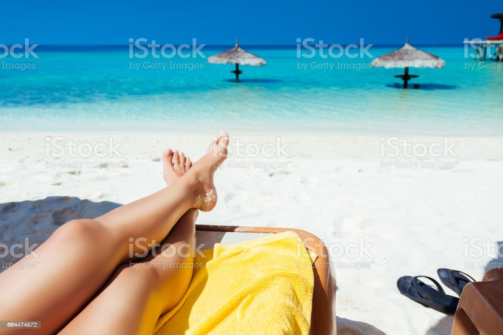 Woman on sunbed reading book under parasol at tropical island stock photo