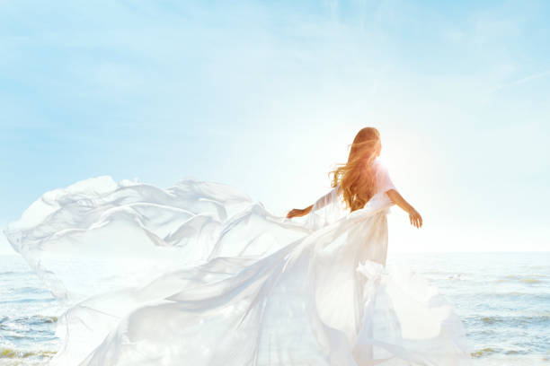Woman on Sunny Sea Beach in White Fluttering Dress, Fashion Model Back Rear View, Silk Cloth Waving on Wind stock photo