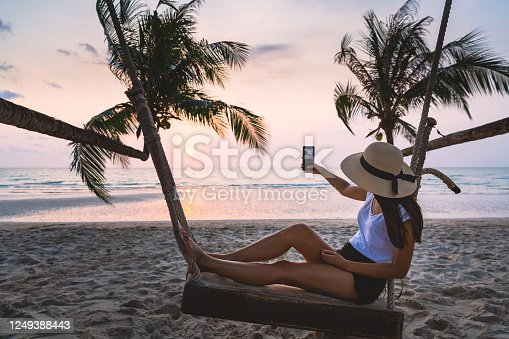 Summer travel vacation concept, Happy traveler asian woman with hat using mobile phone for selfie and relax on swing in tropical beach at sunset, Koh Kood, Thailand