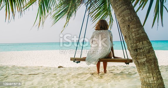 Rear view shot of a woman sitting on a swing hanging from a palm tree on a tropical beach,Maldives