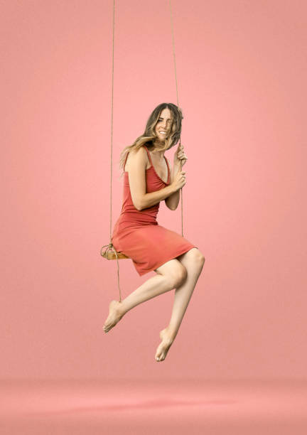 vrouw op schommel op roze achtergrond - schommelen bungelen stockfoto's en -beelden