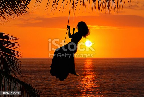 Woman on swing over ocean during sunet
