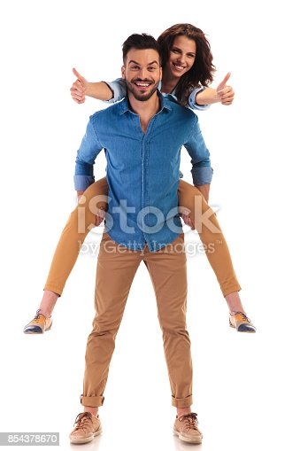 854381886 istock photo woman on the back of her man making  ok sign 854378670