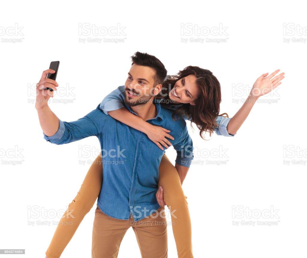 mulher atrás do homem enquanto ele toma selfie - foto de acervo