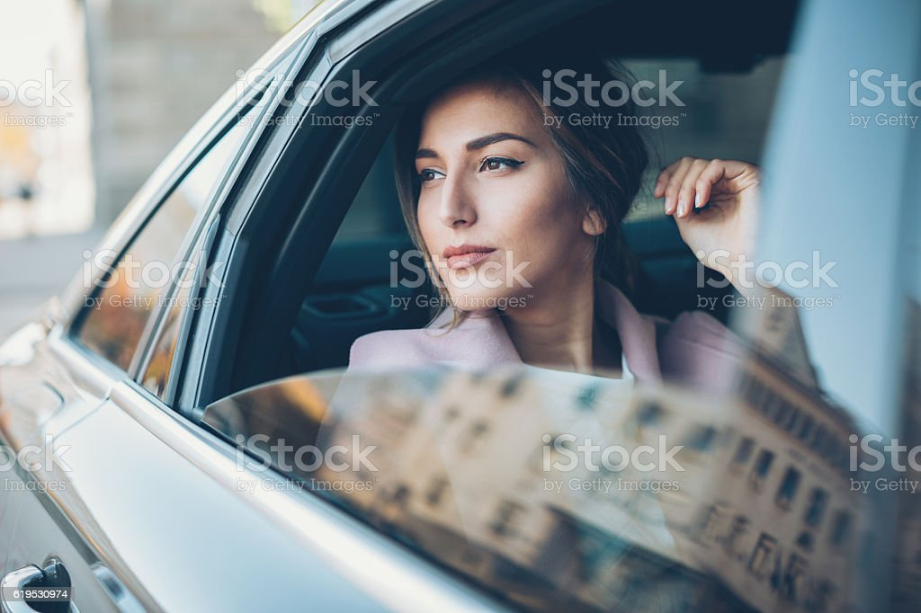 Woman on the back seat of a car stock photo