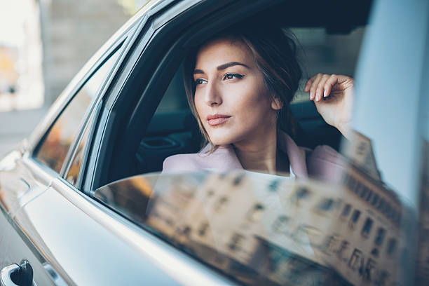 Woman on the back seat of a car - foto de stock