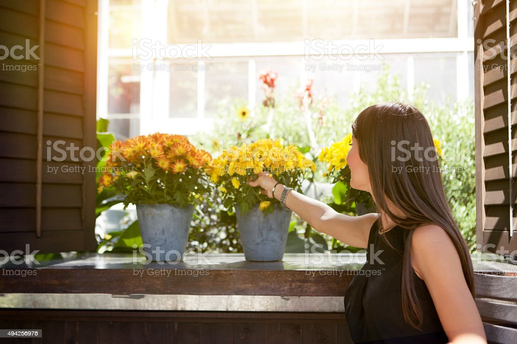 Woman on the balcony enjoy in flowers stock photo