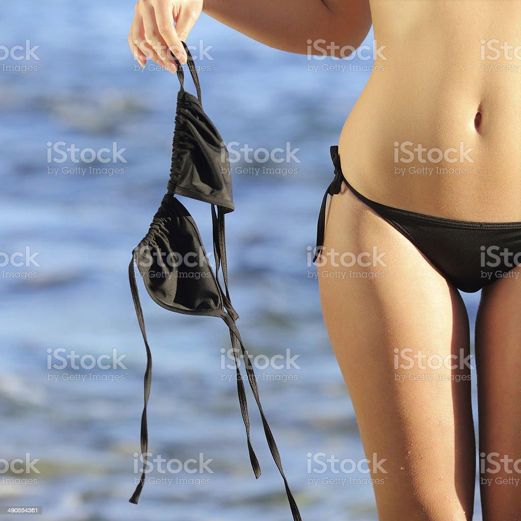 Woman on the beach in topless holding the bikini bra stock photo