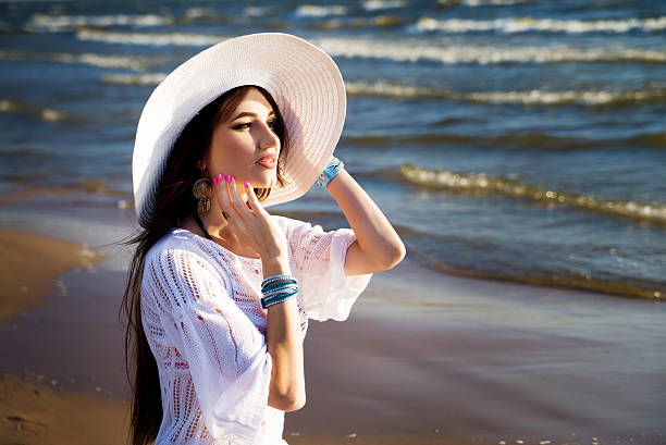 woman on the beach in white hat and lace tunic. - spitzentunika stock-fotos und bilder