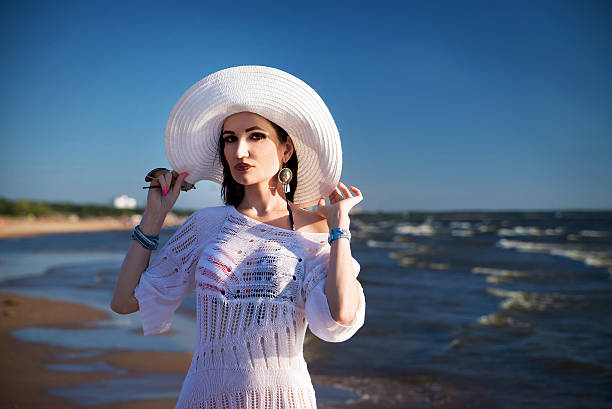 woman on the beach in white hat and lace tunic - spitzentunika stock-fotos und bilder