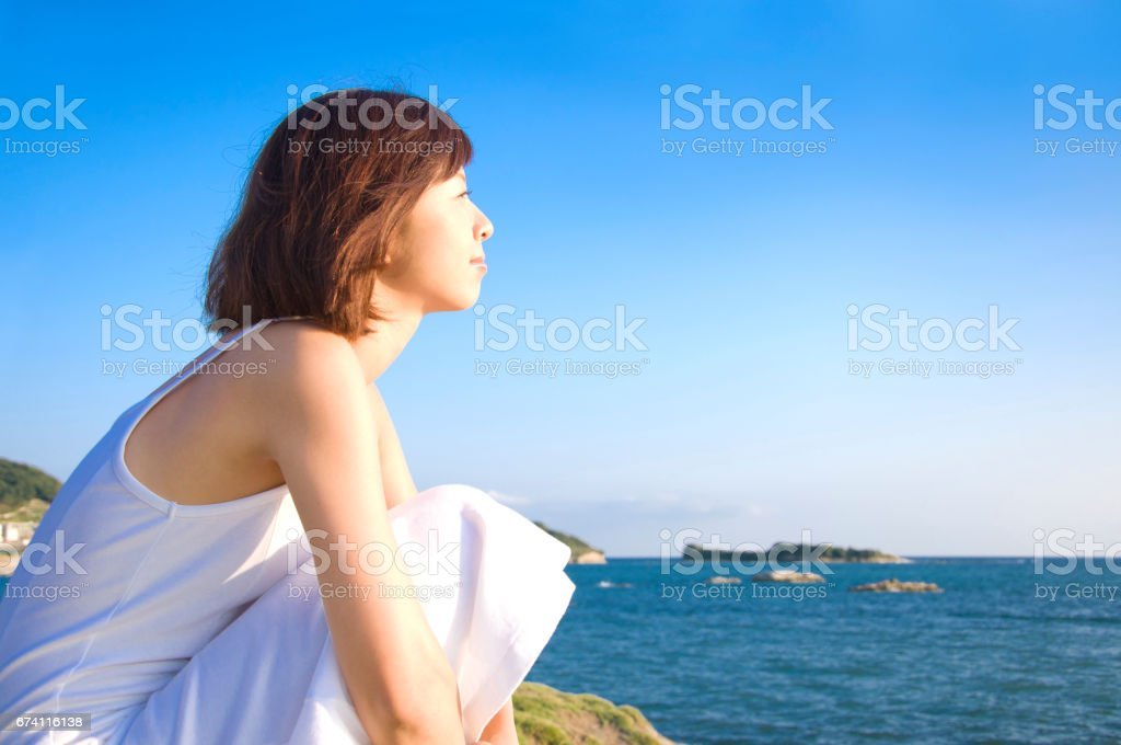 Woman on the beach staring into the distance royalty-free stock photo