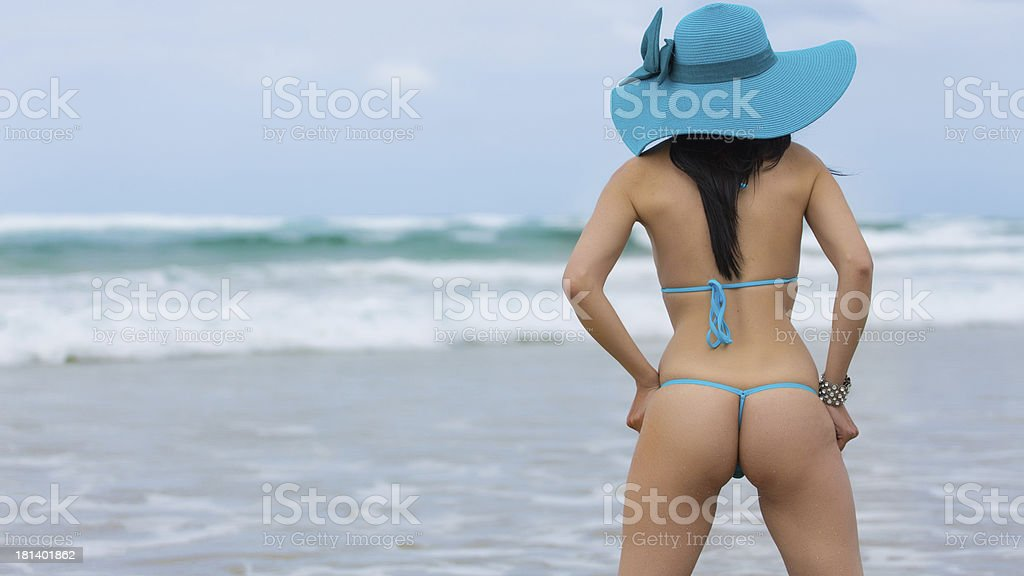 Woman on the beach wearing blue thong bikini stock photo