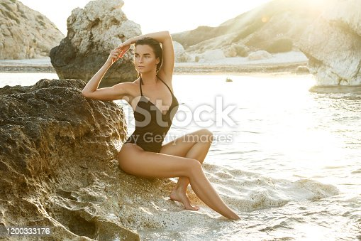 Beautiful woman on the beach with rocks at sunset