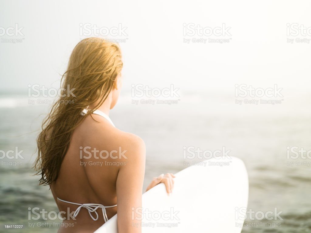 Woman on the beach with surfboard royalty-free stock photo