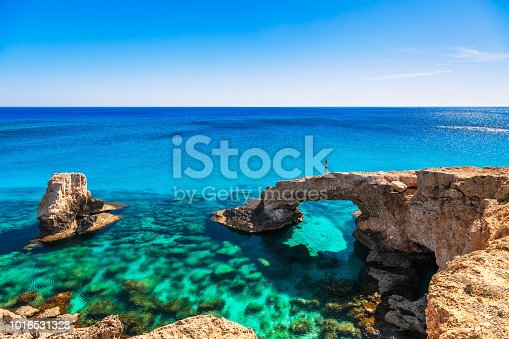 istock Woman on the beautiful natural rock arch near of Ayia Napa, Cavo Greco and Protaras on Cyprus island, Mediterranean Sea. Legendary bridge lovers. Amazing blue green sea and sunny day. 1016531328